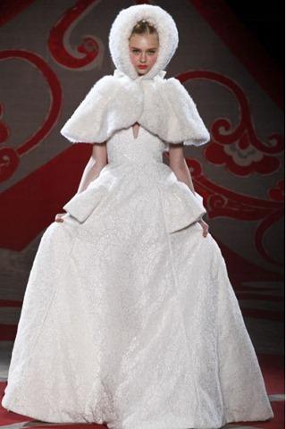 Ульяна Сергеенко показала 2 совершенно противоположных свадебных образа. В первом представлено пышное белое платье и меховая накидка с капюшоном